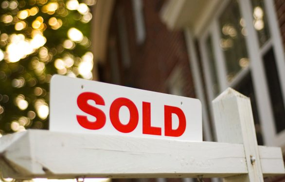 """Real Estate """"sold"""" sign with red brick building and trees blurry in the background"""
